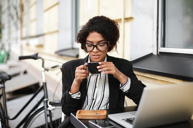 Porträt des afroamerikanischen mädchens in den gläsern, die am tisch des cafés mit laptop sitzen und tasse kaffee in den händen halten