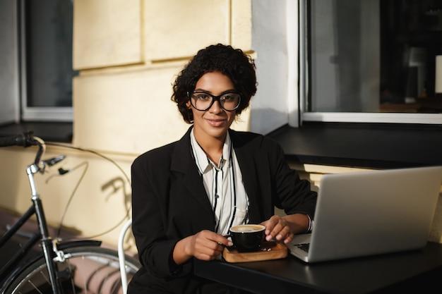 Porträt des afroamerikanischen mädchens in den gläsern, die am tisch des cafés mit laptop und tasse kaffee sitzen