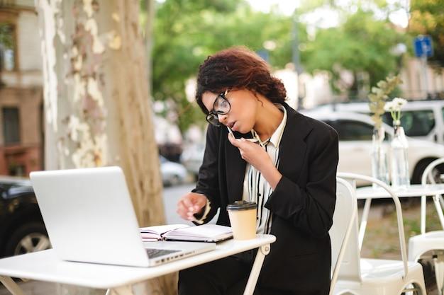 Porträt des afroamerikanischen mädchens in den gläsern, die am tisch des cafés sitzen und auf ihrem handy während der arbeit sprechen