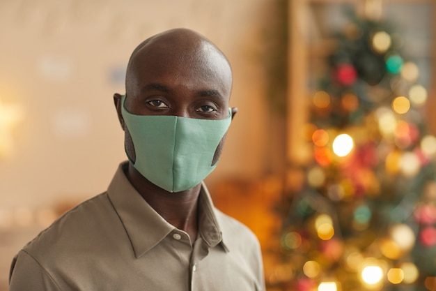 Porträt des afroamerikanischen mannes, der maske trägt und kamera beim feiern von weihnachten, kopienraum betrachtet