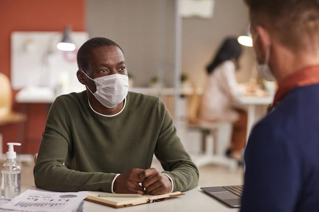 Porträt des afroamerikanischen mannes, der maske während des geschäftstreffens im büro mit flasche des desinfektionsmittels im vordergrund, kopienraum trägt