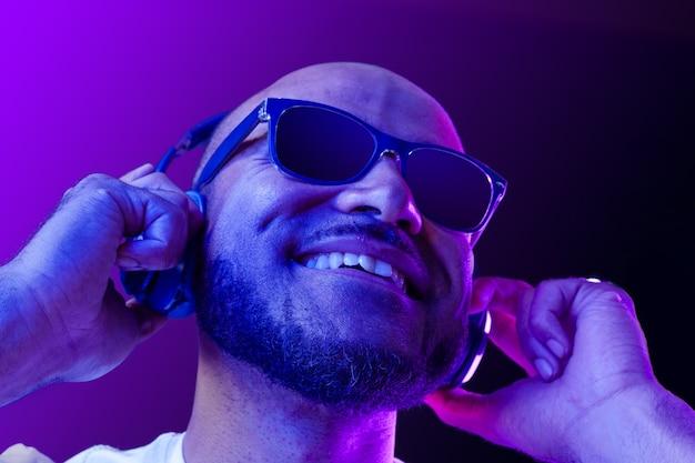 Porträt des afroamerikanischen mannes, der musik im neonlicht nah oben hört