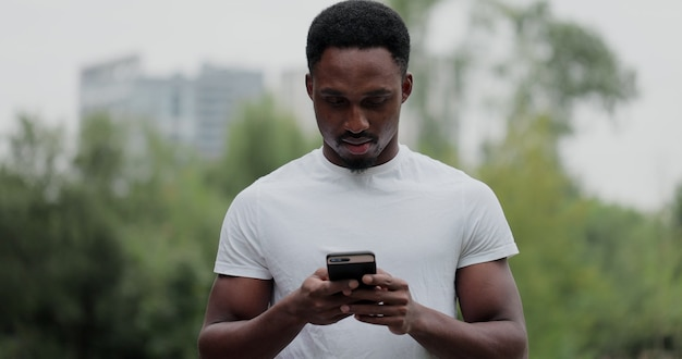 Porträt des afroamerikanischen mannes, der nach dem fitnesstraining eine pause hat. fitness-mann, der sich nach dem laufen die smartphone-fitness-app ansieht.