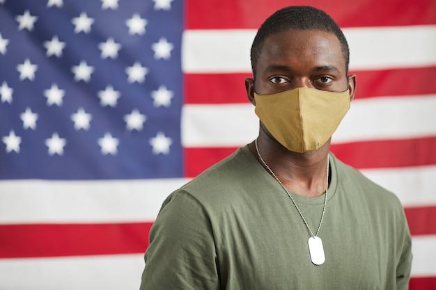 Porträt des afroamerikanischen soldaten in der schutzmaske, die kamera gegen die amerikanische flagge betrachtet