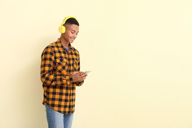 Porträt des afroamerikanischen teenagers, der musik auf farbe hört