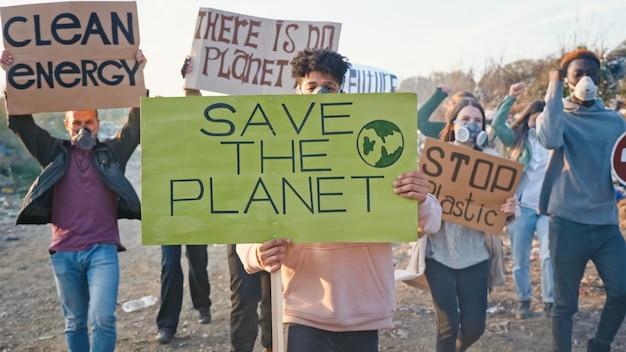 Porträt des aktivisten des jungen mannes mit einem plakat, das dazu aufruft, sich um die umwelt zu kümmern. im hintergrund kämpfende menschen, die gegen die verschmutzung durch müll protestieren, die auf einer müllkippe am stadtrand bleiben.