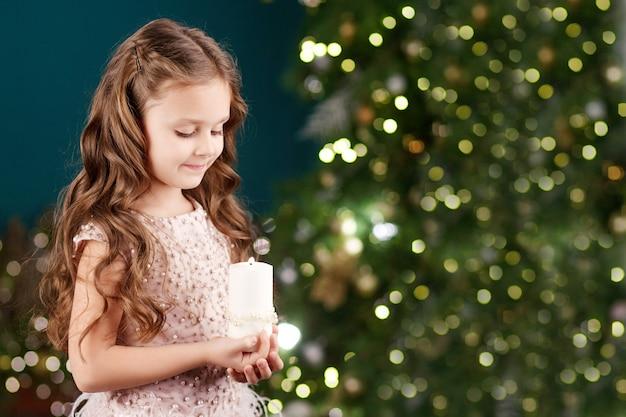 Porträt des akuten langhaarigen kleinen mädchens im kleid mit lichtern. kleines mädchen, das brennende kerze hält. weihnachts-, neujahrs- und geburtstagsfeierkonzept. winterferien. speicherplatz kopieren
