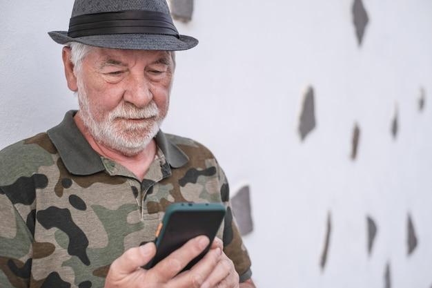 Porträt des alten attraktiven älteren mannes mit traurigem ausdruck unter verwendung des handys. weißhaariges gesicht mit bart. isoliert auf weißem hintergrund