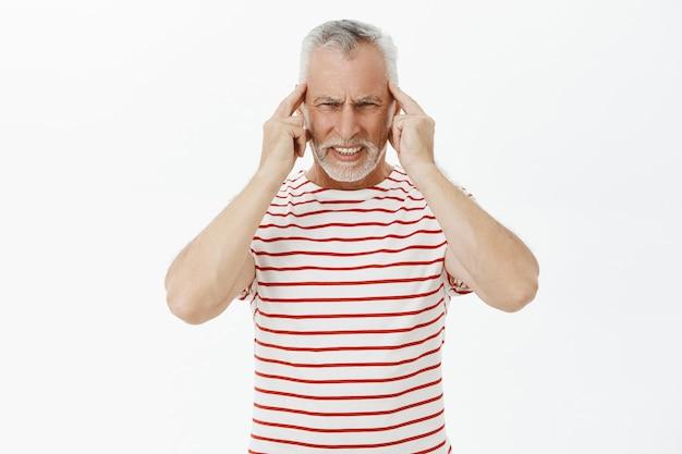 Porträt des alten bärtigen mannes, der den kopf berührt, über kopfschmerzen klagt, migräne hat