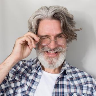 Porträt des alten mannes, der brille hält