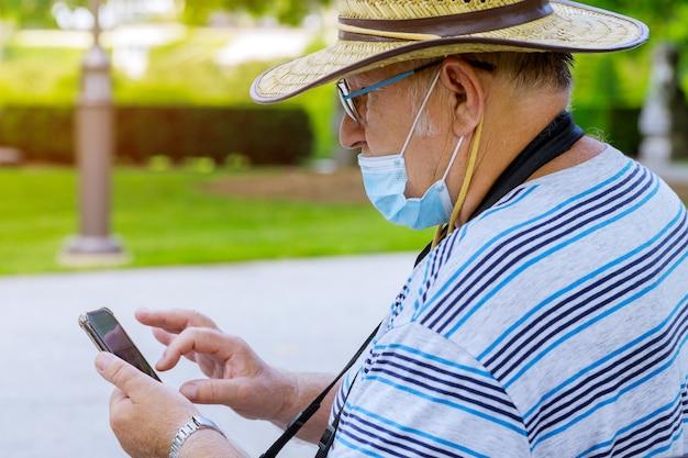 Porträt des alten mannes eine tragende medizinische maske mit dem verwenden des smartphones während des hörens schützen während des coronavirus covid-19 in einem park