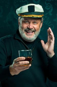 Porträt des alten seemannsmannes als kapitän im schwarzen pullover und im hut, der cognac auf schwarzem studio trinkt