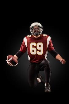 Porträt des amerikanischen fußballspielers, der einen ball mit beiden händen hält
