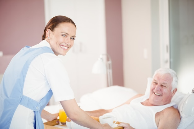 Porträt des angebotsfrühstücks der krankenschwester zum älteren mann, der auf bett liegt