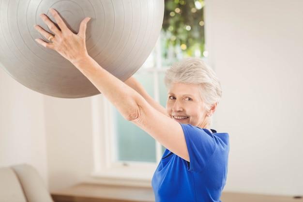 Porträt des anhebenden übungsballs der älteren frau beim zu hause trainieren