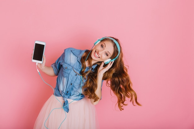 Porträt des anmutigen glücklichen mädchens in den großen kopfhörern, die tanzen und spaß lokalisiert auf rosa hintergrund haben. charmante süße junge frau im rock mit lockigem haar winkt, hält telefon genießt lieblingslied