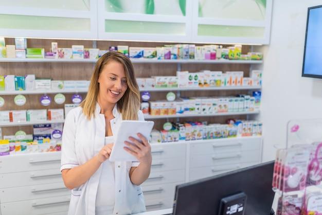Porträt des apothekers digitale tablette in der apotheke halten