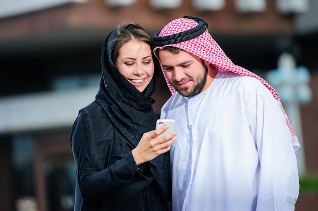 Porträt des arabisch gekleideten yang-paares spielen mit handy.