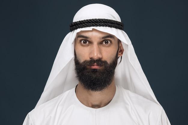 Porträt des arabischen saudi-scheichs. junges männliches modell posiert und sieht ernst oder ruhig aus.