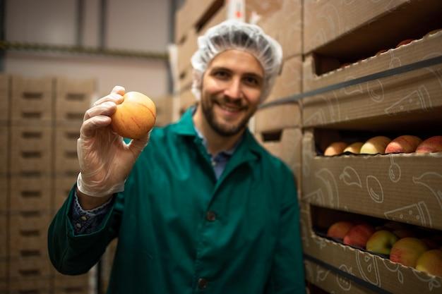 Porträt des arbeiters, der apfelfrucht im lagerhaus der bio-lebensmittelfabrik hält.