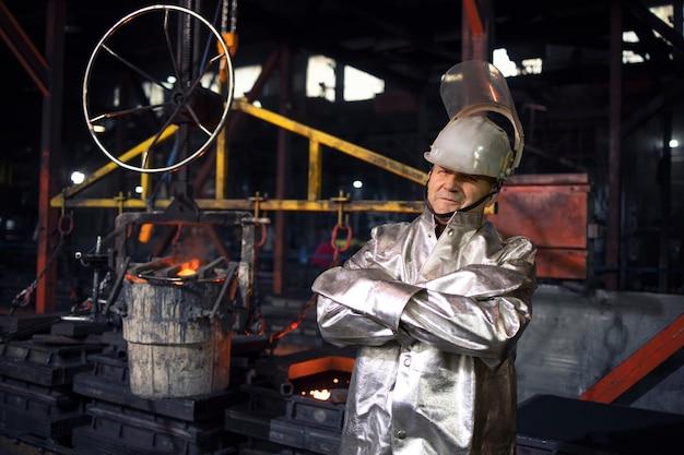 Porträt des arbeiters im aluminisierten hochtemperaturschutzanzug mit verschränkten armen stehend in der gießereistahlproduktionsfabrik.