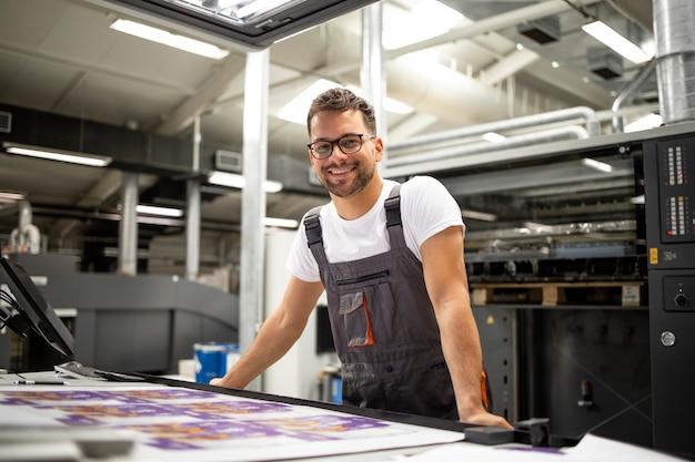 Porträt des arbeiters im kontrollraum, der die druckqualität in der druckerei überprüft.