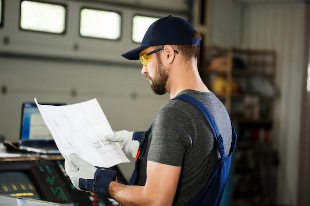Porträt des arbeiters im overall, hintergrund der stahlfabrik.