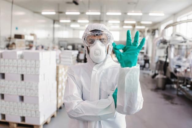 Porträt des arbeiters in der schutzuniform mit gummihandschuhen, die im lager stehen und okayes zeichen mit hand zeigen. konzept des corona-virus-ausbruchs.