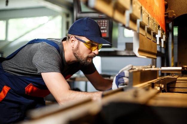 Porträt des arbeiters nahe der metallbearbeitungsmaschine