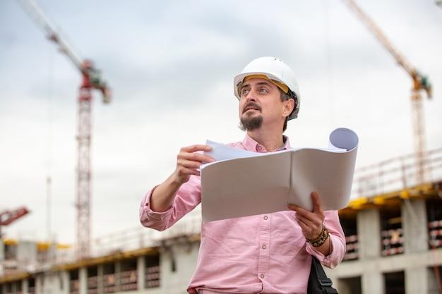 Porträt des architekten bei der arbeit mit helm auf einer baustelle, liest den plan, papierprojekte