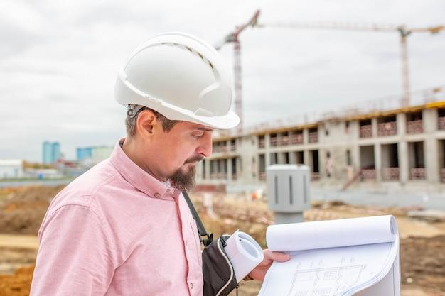 Porträt des architekten bei der arbeit mit helm auf einer baustelle, liest den plan.