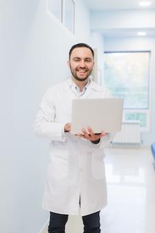 Porträt des arztes, der laptop auf flur hält