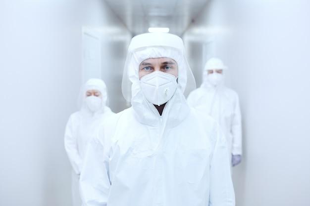 Porträt des arztes in schutzkleidung, der während der pandemie im krankenhausflur steht