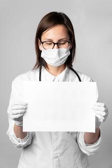 Porträt des arztes mit der chirurgischen maske, die ein zeichen hält
