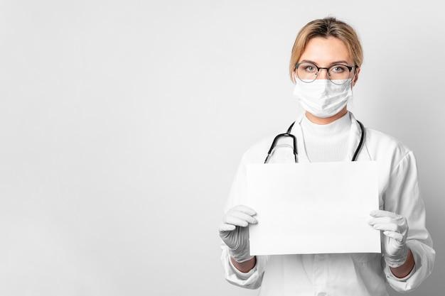 Porträt des arztes mit der chirurgischen maske, die leeres papier hält
