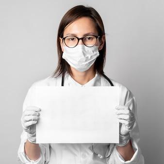 Porträt des arztes mit der chirurgischen maske, die papier hält