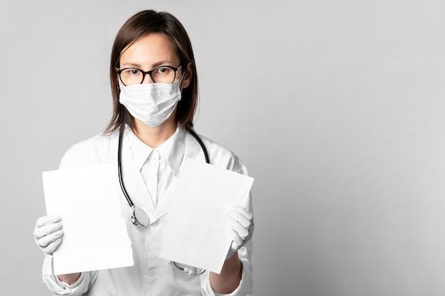 Porträt des arztes mit der chirurgischen maske, die papiere hält