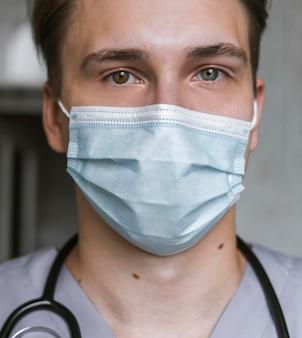 Porträt des arztes mit stethoskop und medizinischer maske