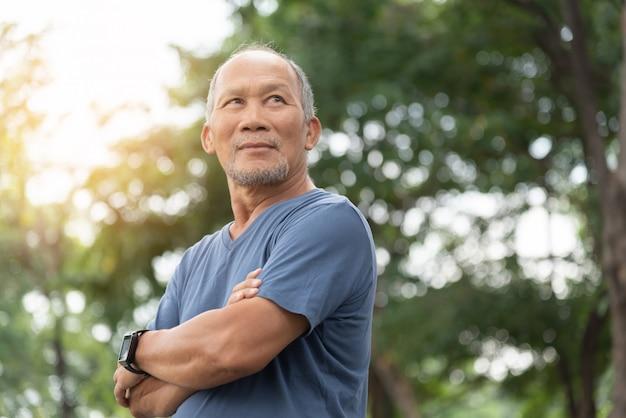 Porträt des asiatischen älteren mannes mit verschränkten armen, die über naturhintergrund entspannen. glückliche selbstbewusste ältere person im blauen hemd, das am park steht.