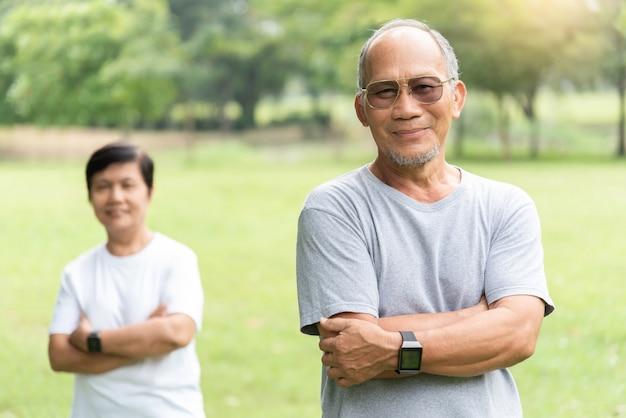 Porträt des asiatischen älteren paares, das mit verschränkten armen vor dem training lächelt.