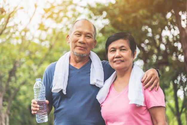 Porträt des asiatischen älteren paares im blauen und rosa hemd lächelnd und stehend am park im freien.