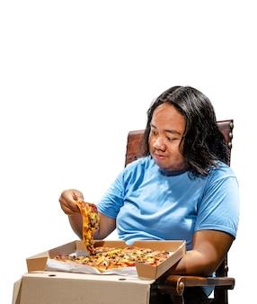 Porträt des asiatischen dicken mannes, der scheibe pizza sitzt und isst