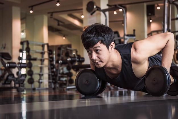 Porträt des asiatischen eignungsmannes, den das handeln drückt, übung mit dummkopf in der turnhalle hoch.