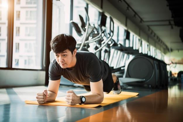 Porträt des asiatischen eignungsmannes, der plankenübung in der turnhalle tut