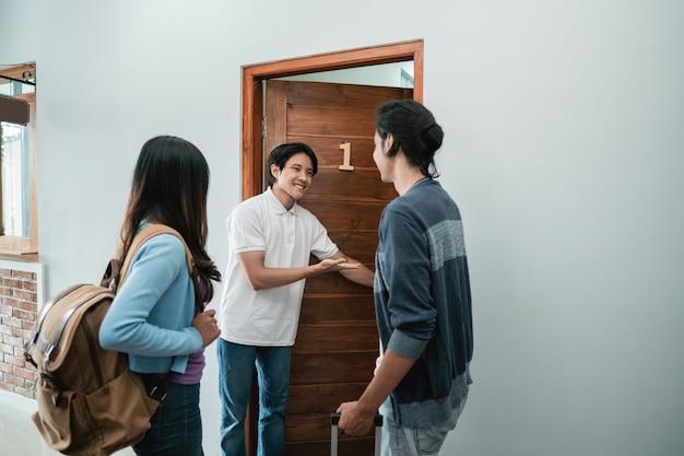 Porträt des asiatischen gästehauspersonals, das paar im boutique-hotel begrüßt