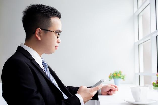 Porträt des asiatischen geschäftsmannes, der einen smartphone in der kaffeestube verwendet.