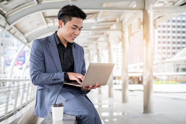 Porträt des asiatischen geschäftsmannes laptop und kaffeetasse in der gebäudebürostadt halten
