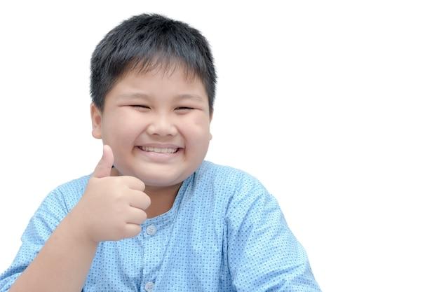 Porträt des asiatischen glücklichen fetten jungen, der daumen zeigt, up geste, lokalisiert über weißem hintergrund