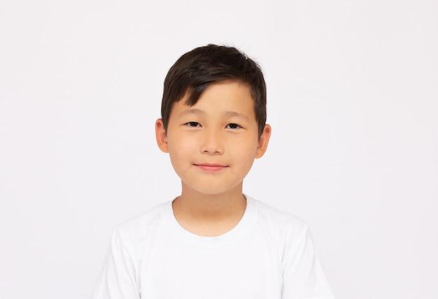 Porträt des asiatischen glücklichen jungenlächelngesichtes und des betrachtens der kamera auf weißem hintergrund