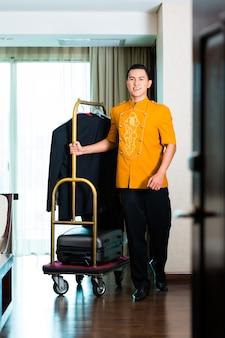 Porträt des asiatischen jungen, der kastenpackwagen zieht